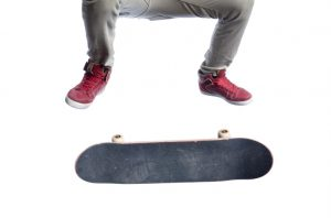 """Skateboarder wearing tan skinny jeans and red hi-top skateshoes. Framed from the waist down. Ollie kick flip, board in mid flip. Isolated on white."""