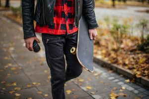 Hipster holding a coffee cup and a skateboard while walking in the park in autumn.